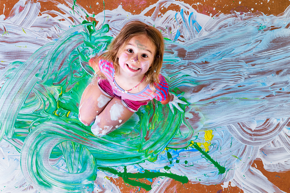 Creative paint splattered little girl having fun with paints kneeling in the center of her artistic modern painting grinning up at the camera, overhead view